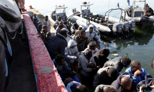 Migrants sit in a port, after being rescued at sea by Libyan coast guard, in Tripoli